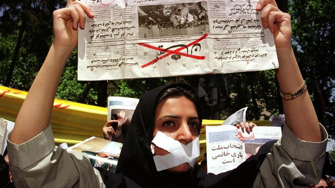 An Iranian student wears tape over her mouth and indicates her objection to the conservative press by holding a copy of the conservative daily Keyhan with the title crossed out. (File photo: AFP)