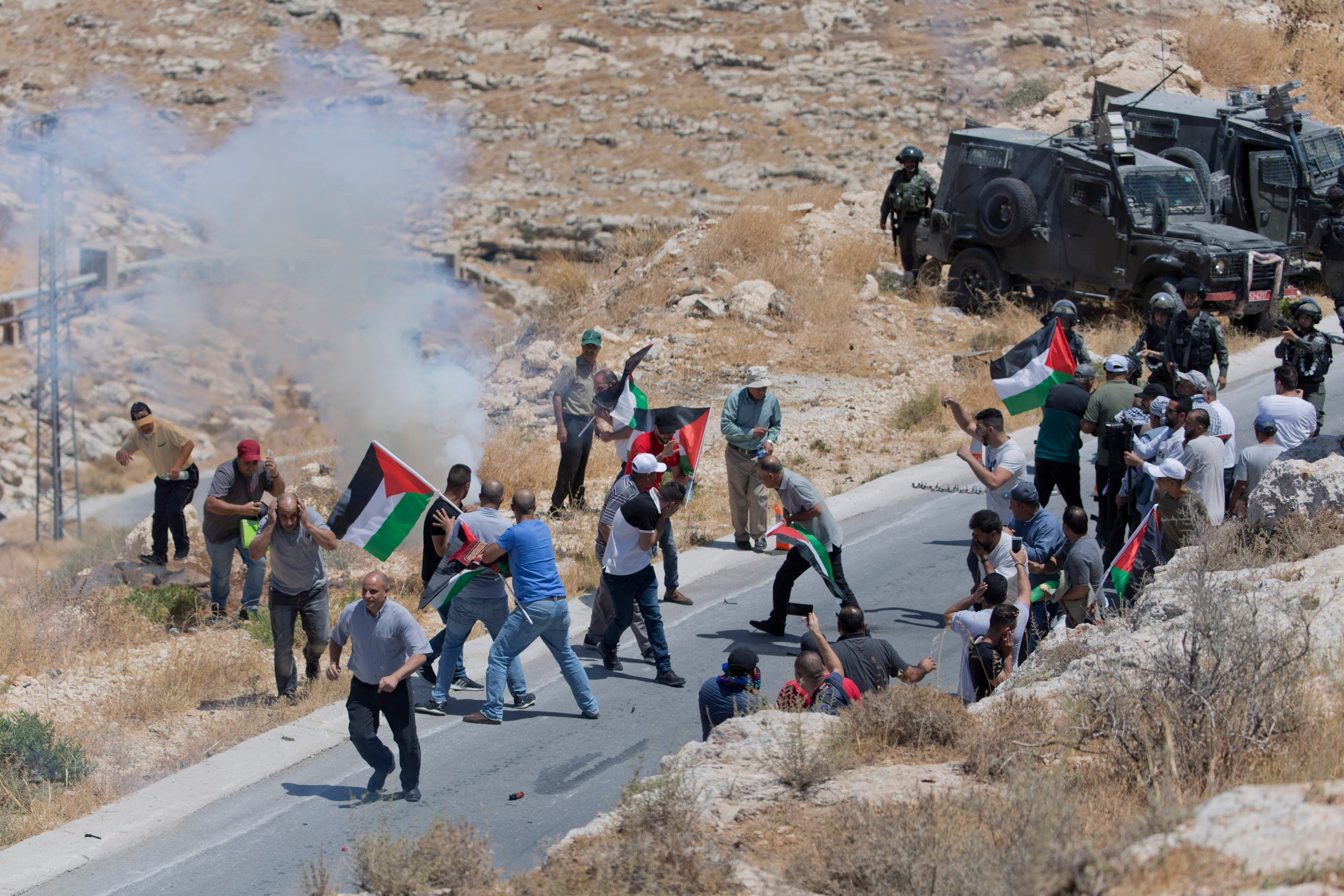 Israeli border police block the road and disperse Palestinian, Israeli and foreign activists during a rally protesting a newly established settlement near the West Bank village of Kufr Malik on Aug. 16. 2019. (AP)