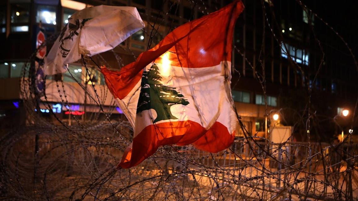 The Lebanese flag hangs on barbed wire blocking a road leading to the parliament building in downtown Beirut on November 18, 2019. (AFP)