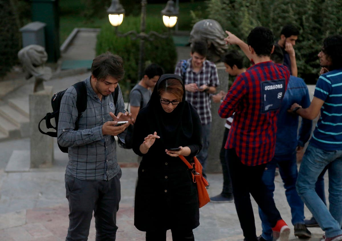 Iranian youths with their smart phones in northern Tehran's Mellat Park on August 3, 2016. (File photo: AFP)