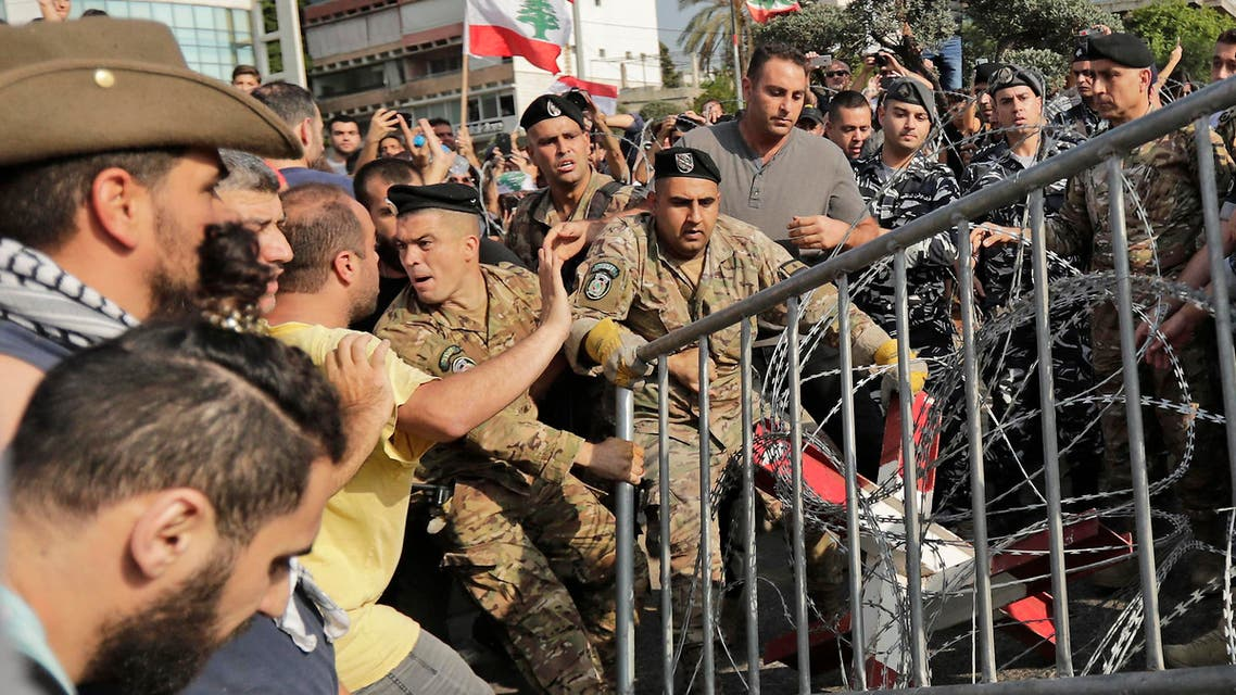 Scenes from Lebanese protesters trying to remove security barriers outside Baabda palace on November 13 (AFP)