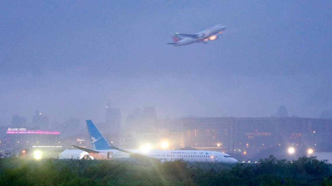 A Philippine Airlines passenger plane takes off while a Boeing passenger plane from China, a Xiamen Air, lies on the grassy portion of the runway. (File photo: AP)