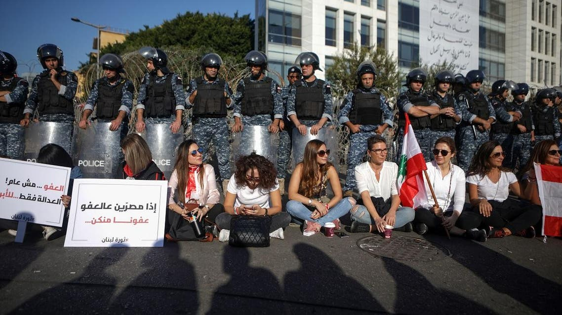Lebanese anti-government protesters sit on the ground as they take part in a demonstration near the parliament headquarters in the capital Beirut's downtown district on November 19, 2019. (AFP)