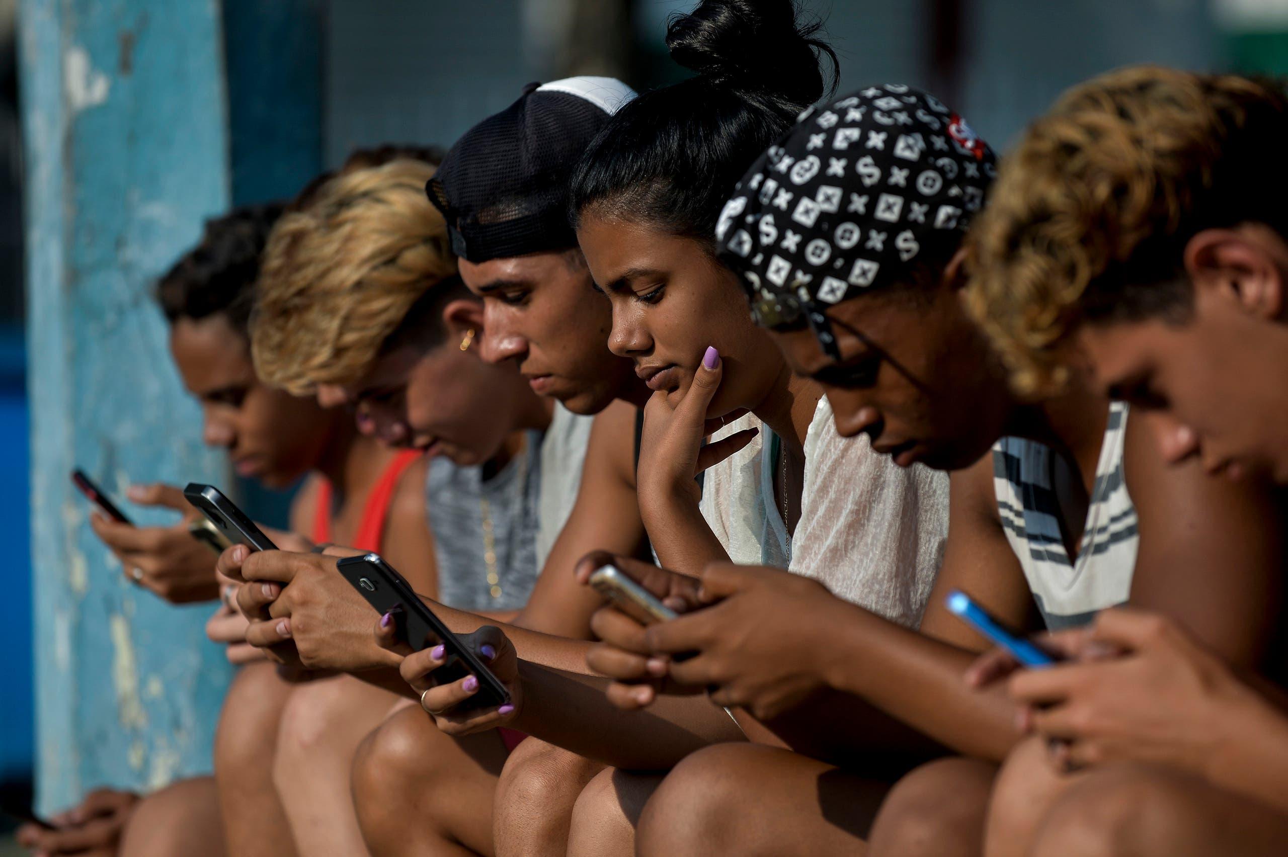 Teenagers using their phones. (AFP)
