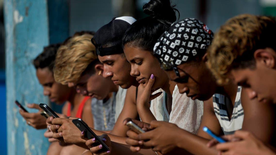 teenagers using their phones (AFP)
