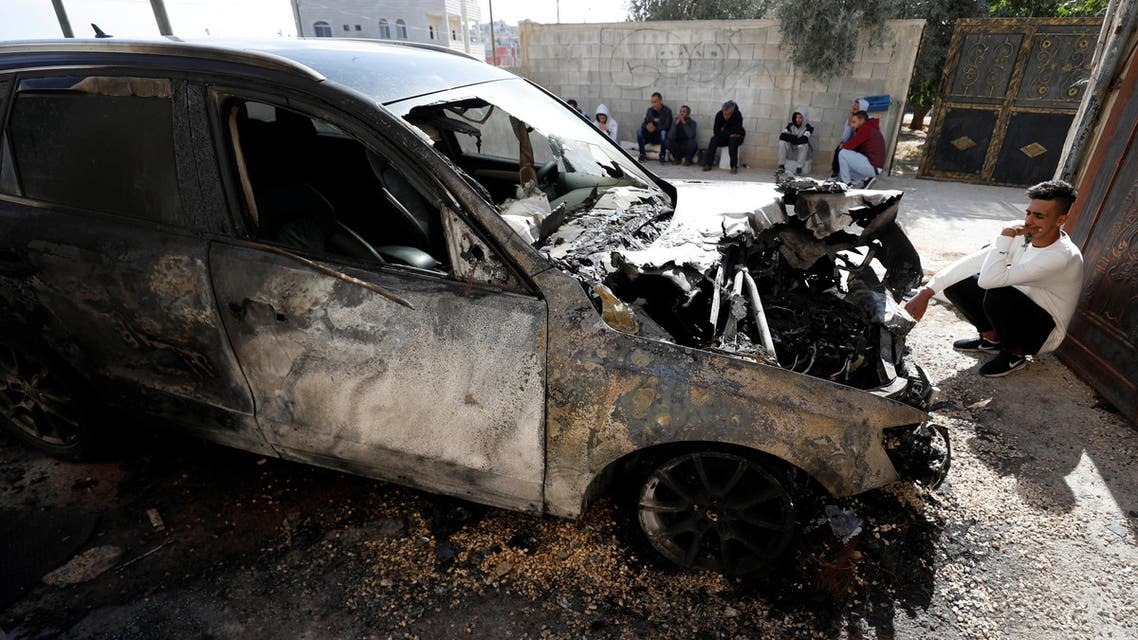A Palestinian sits next to a vehicle that was set on fire in the southern Nablus, in the Israeli-occupied West Bank (Reuters).jpg
