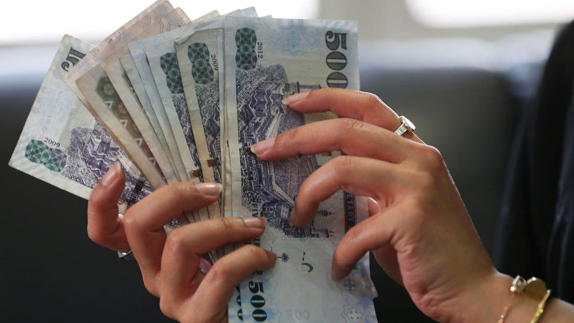 A Saudi woman shows Saudi riyal banknotes at a money exchange shop in Riyadh - Reuters