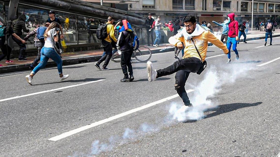 A demonstrator kicks a tear gas canister during a protest against the government of Colombia's President Ivan Duque, in Bogota, on November 23, 2019. (AFP)
