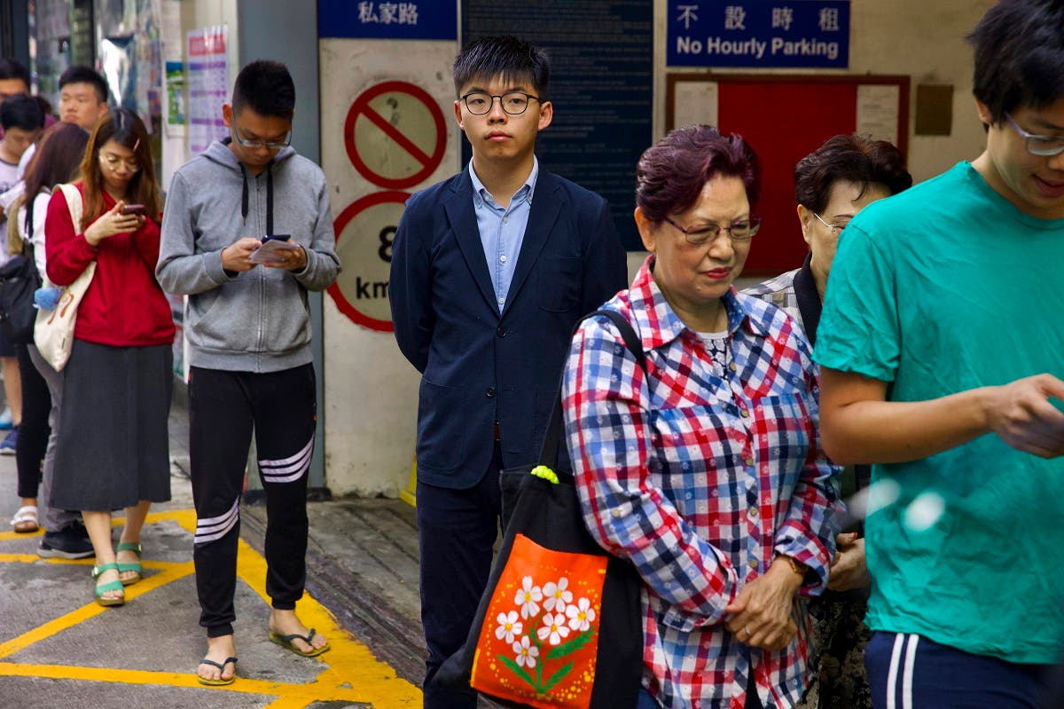 Pro-democracy activist Joshua Wong, center, stands in line to vote outside of a polling place in Hong Kong, Sunday, Nov. 24, 2019. (AP)