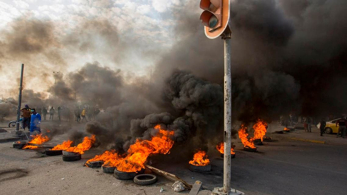 Smoke billows from burning tires during a demonstration in the southern city of Basra on November 24, 2019, as protesters cut-off roads and activists call for a general strike. (AFP)