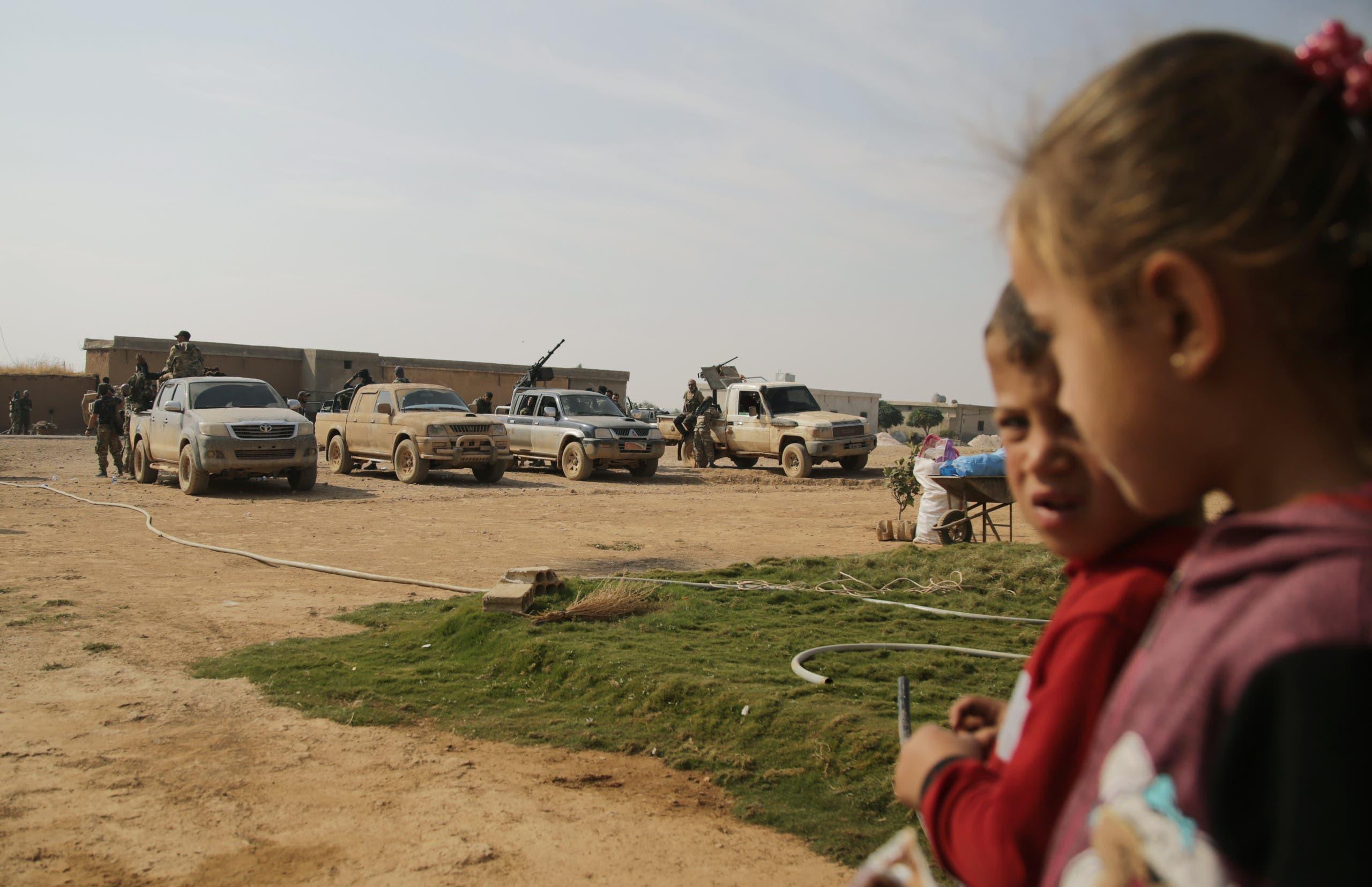أطفال في تل أبيض أمام آليات عسكرية للفصائل الموالية  لتركيا (فرانس برس)