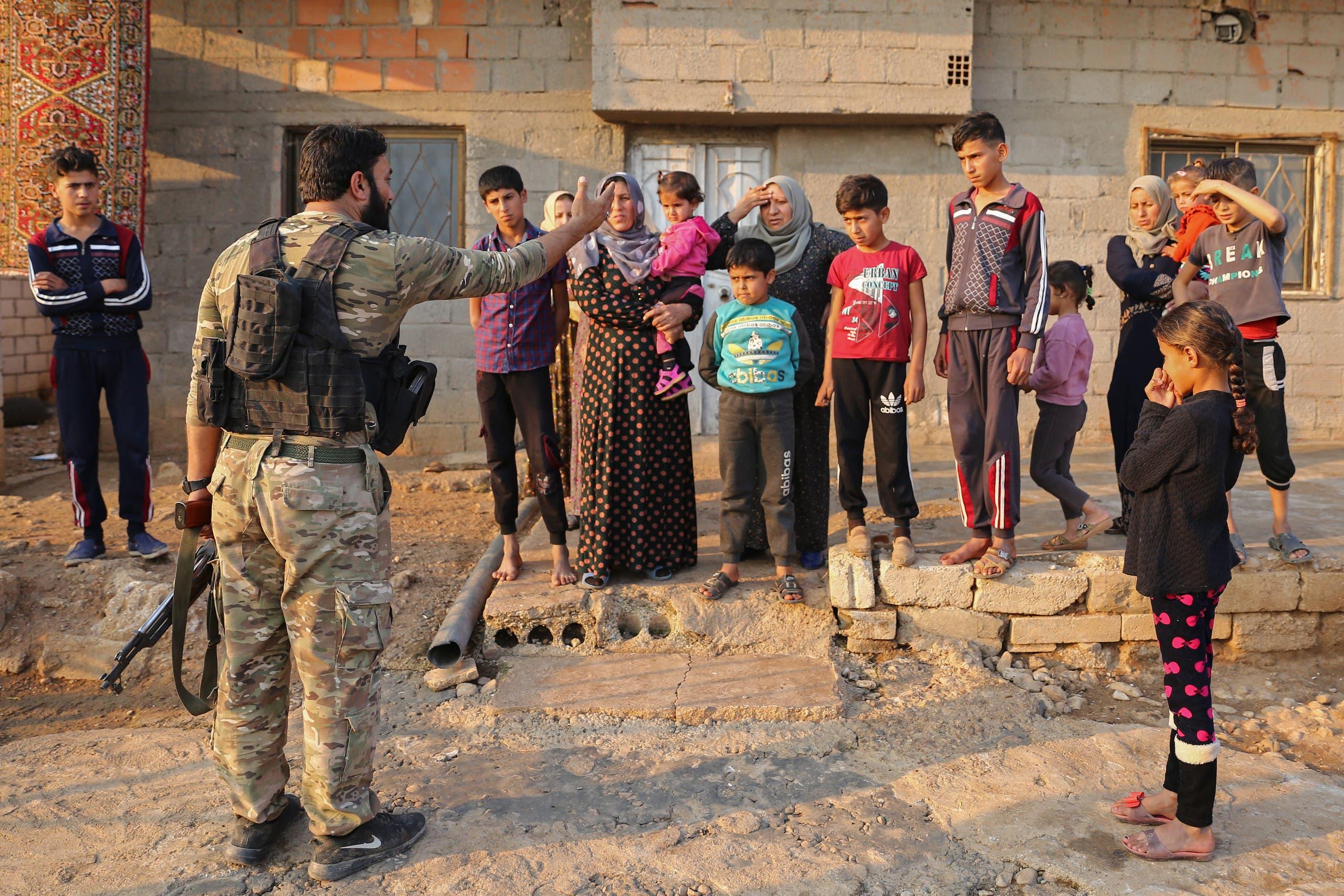 أطفال وسكان في رأس العين يستجوبهم أحد عناصر الفصائل المسلحة الموالية لتركيا (فرانس برس)