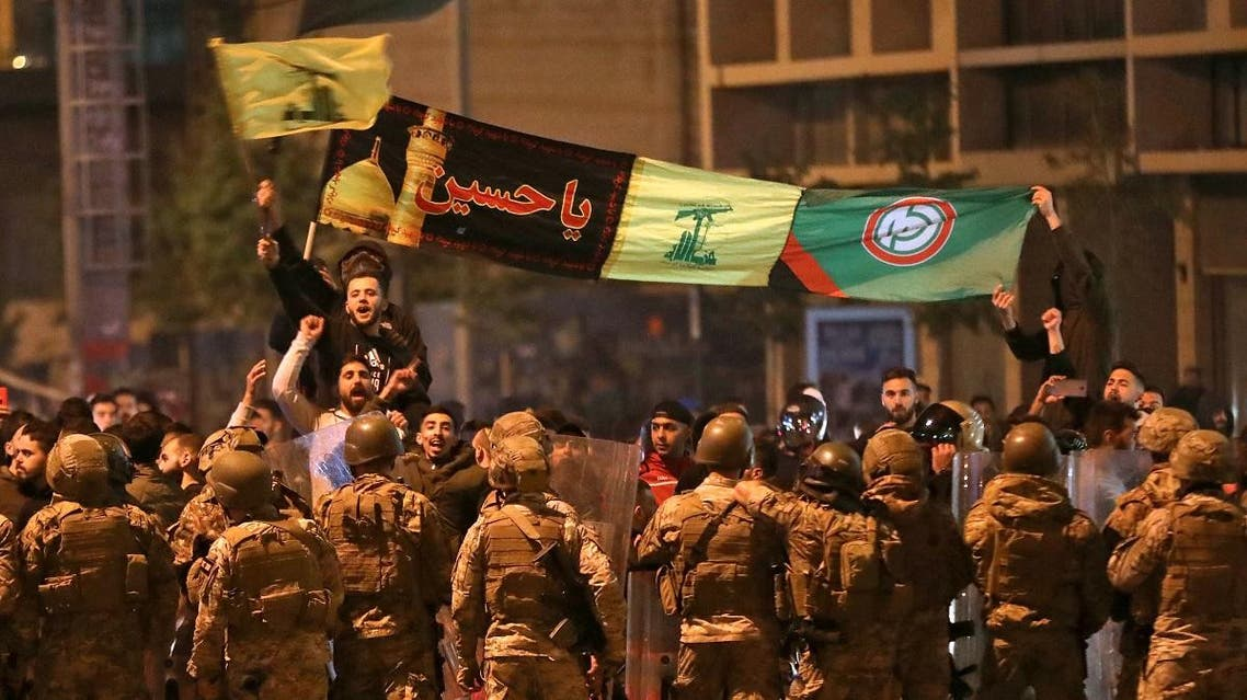 Supporters of Lebanese Shia groups Hezbollah and Amal wave flags and chant in front of army soldiers in the capital Beirut, on November 25, 2019. (AFP)