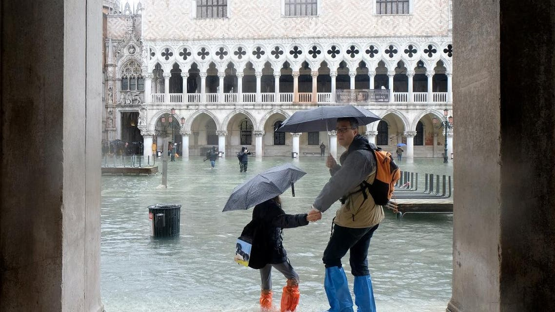 People walk in a flooded St. Mark's Square during a period of seasonal high water in Venice, Italy November 24, 2019. REUTERS