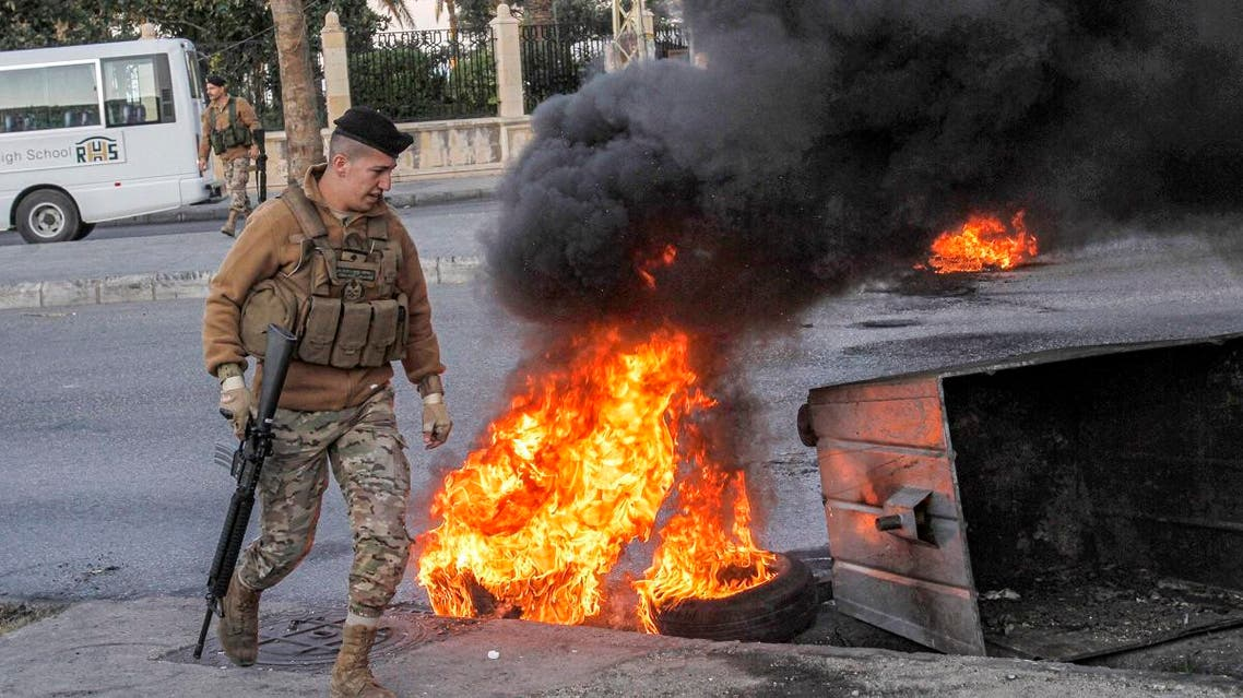 A Lebanese army soldier walks past flaming tires next to a dumpster set by anti-government protesters to block roads in the southern city of Sidon on November 19, 2019, ahead of the Lebanese parliament convening for a session in the capital Beirut. Mahmoud ZAYYAT / AFP