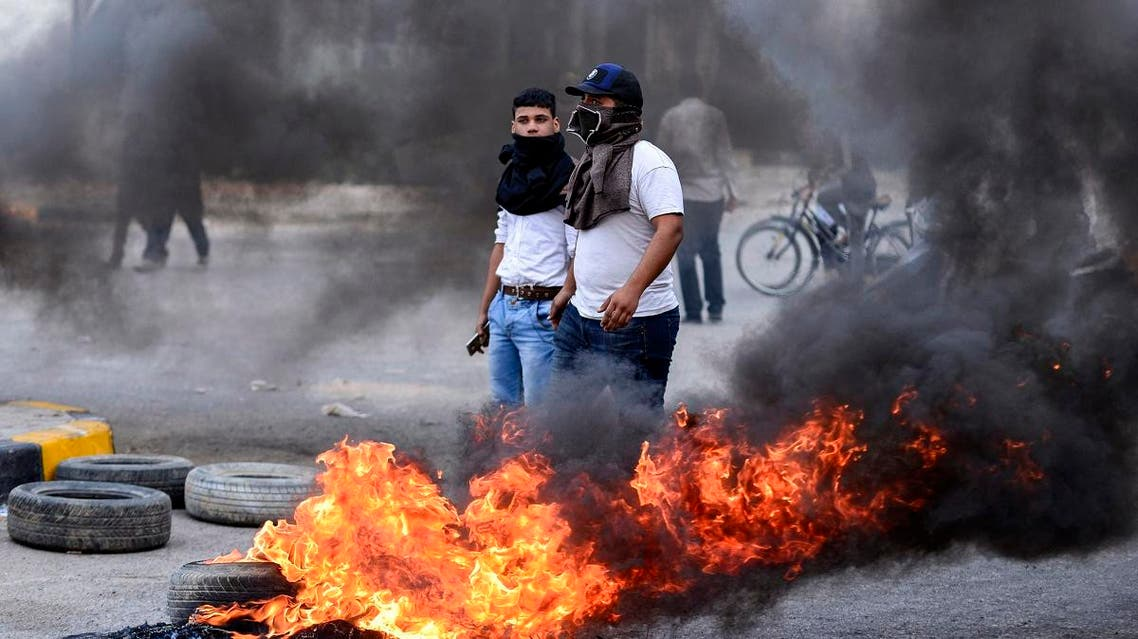 Masked Iraqi protesters stand next to burning tires at a roadblock in the central holy shrine city of Najaf on November 18, 2019. Haidar HAMDANI / AFP