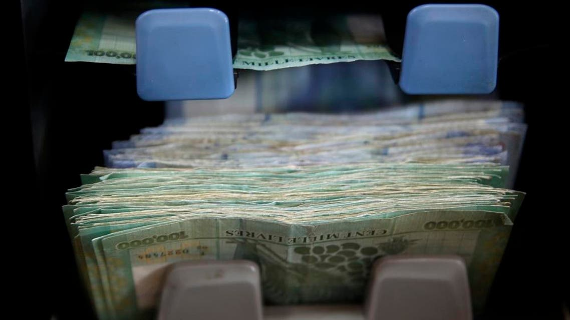 Lebanese currency is counted on a machine at an currency exchange shop, in Beirut credit ap