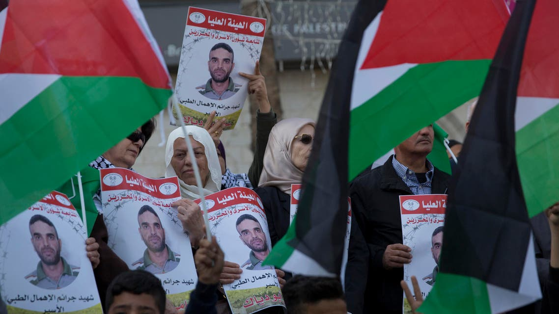 Protesters fly Palestinian flags and carry posters with pictures of Palestinian prisoner in Israeli jail, Sami Abu Diak, who died this morning, during a protest in the West Bank city of Ramallah, Tuesday, Nov. 26. 2019 (AP)