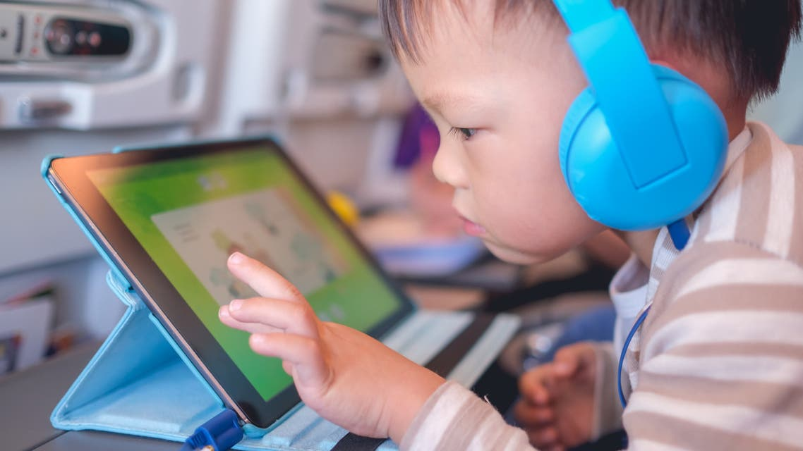 Asian 2 - 3 years old toddler boy child wearing headphones using tablet pc watching cartoons / playing game during flight on airplane stock photo