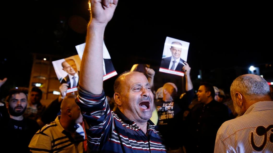 Supporters of Lebanese President Michel Aoun chant slogans as they hold his pictures during a protest near the presidential palace in the Beirut suburb of Baabda, Lebanon, Tuesday, Nov. 26, 2019. (AP)