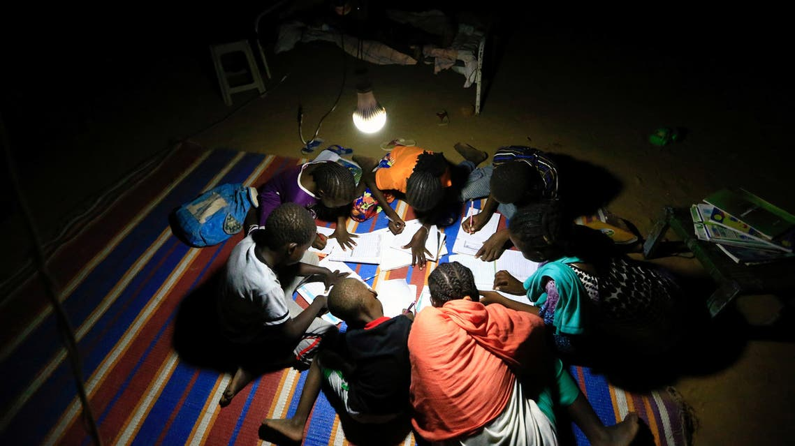 Reuters- Students use a bulb powered by a car battery to do their homework in Al Fashir in North Darfur, Sudan