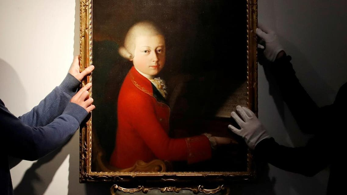 Workers install a portrait due to be sold at auction by Christie's on November 27 which depicts composer Wolfgang Amadeus Mozart as a teenager, painted in January 1770, and attributed to Veronese master Gaimbettino Cignaroli, in Paris. (Reuters)