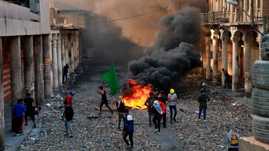 Anti-government protesters set fire while security forces close Rasheed Street during clashes in Baghdad, Iraq. (AP)