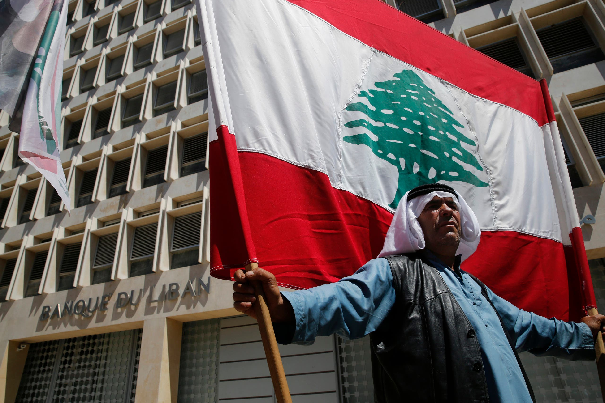 A retired Lebanese soldier holds a national flag, during a protest in front the central bank headquarters, in Beirut, Lebanon, Monday, May 13, 2019. (AP)