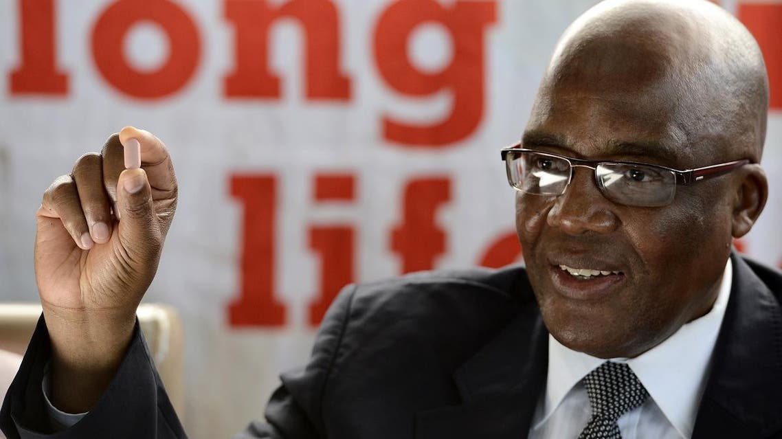 South Africa's Health Minister Aaron Motsoaledi holds the three-in-one combination anti-retroviral (ARV) pill on April 8, 2013 during the launch of the new single dose anti-AIDs drug at Phedisong clinic in Ga-Rankuwa, 100 kms north of Johannesburg. (AFP)