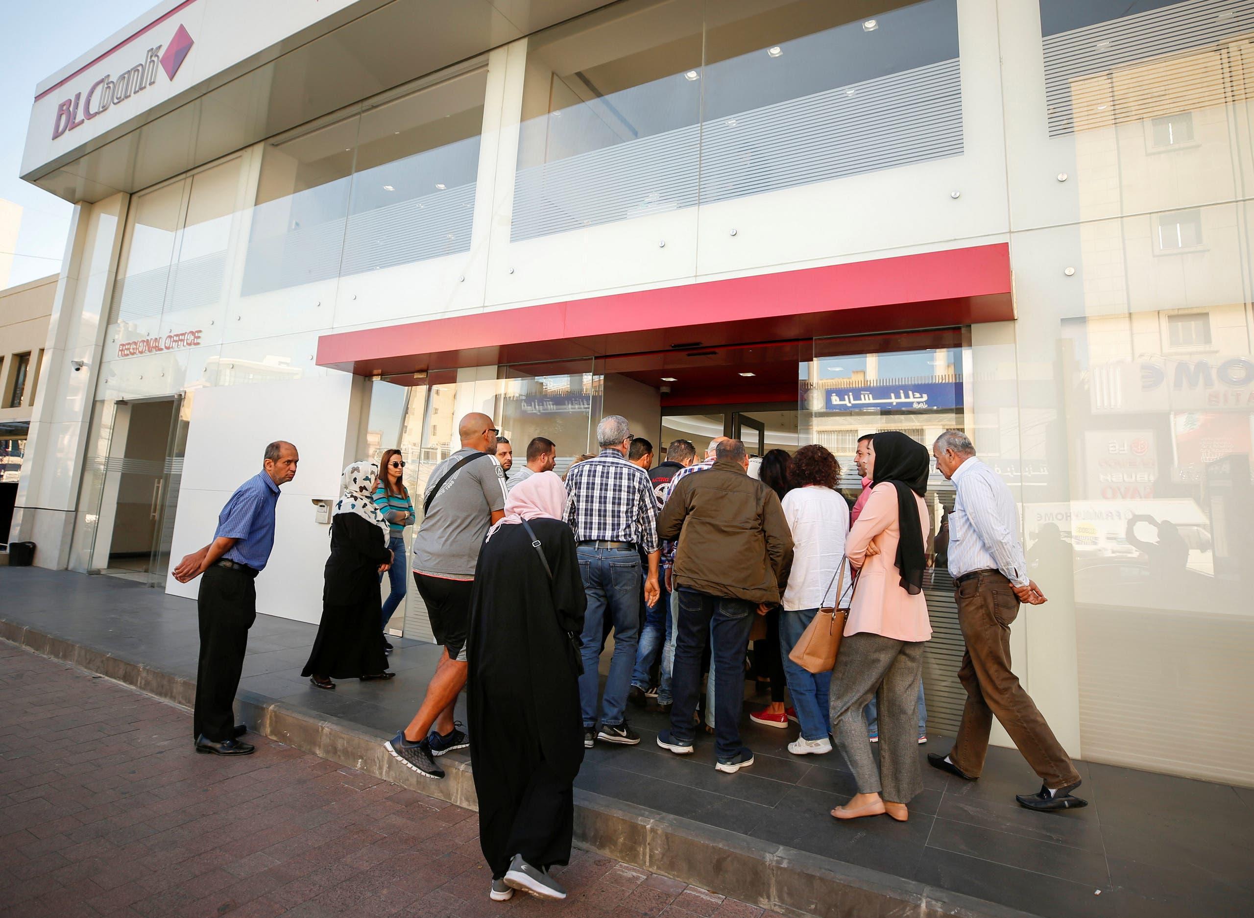 أشخاص يقفون خارج أحد البنوك في صيدا بلبنان