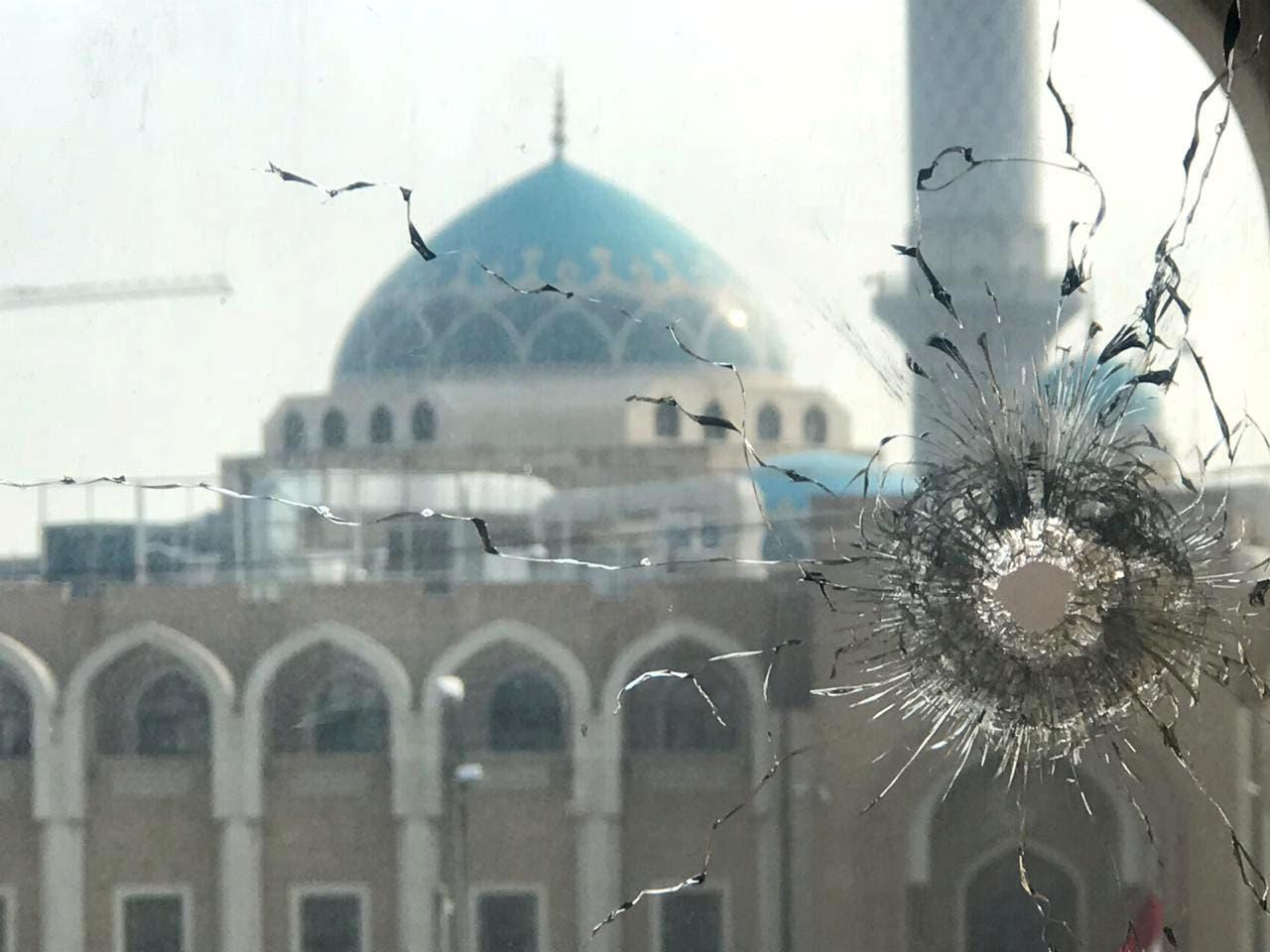 نافذة مكسورة أمام مرقد الحكيم خلال الاحتجاجات في النجف