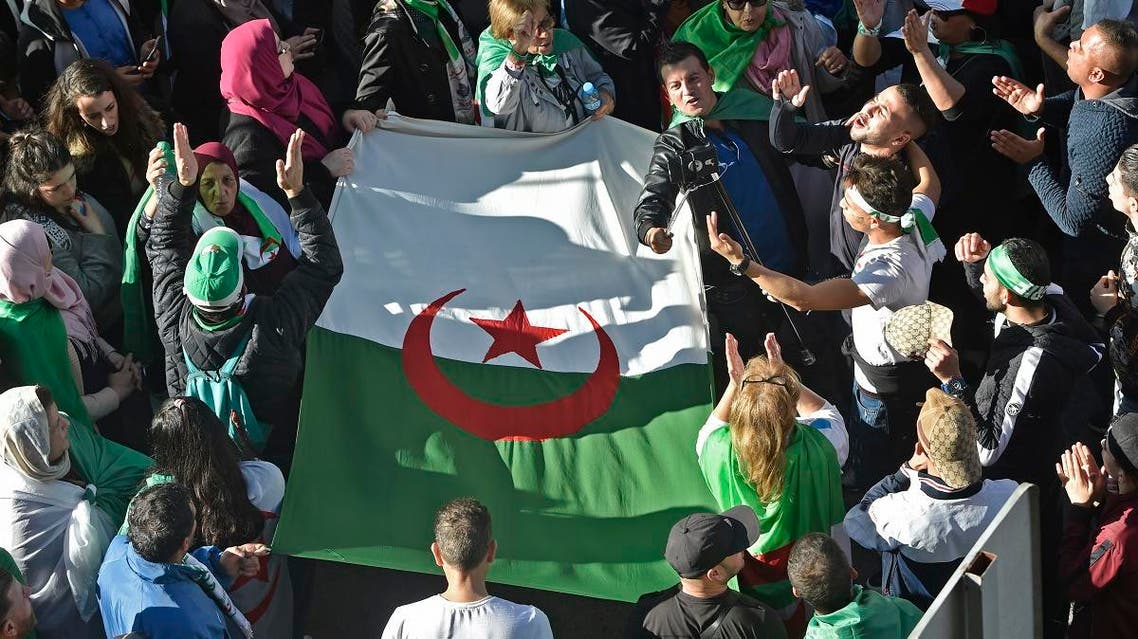 Algerian demonstrators carry a large national flag as they take part in an anti-government protest in the capital Algiers on November 29, 2019. (AFP)