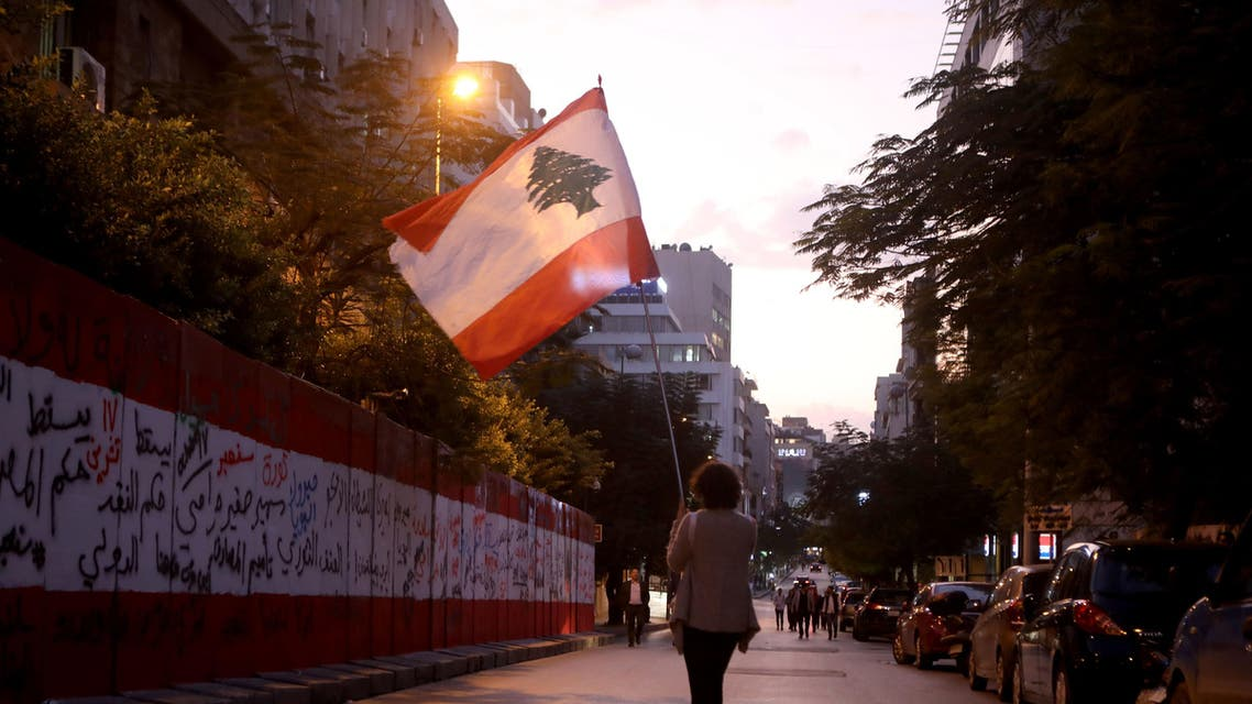 A Lebanese anti-government protester walks with her national flag during a demonstration outside the headquarters of Lebanon's Central Bank in the capital Beirut on November 28, 2019. (AFP)