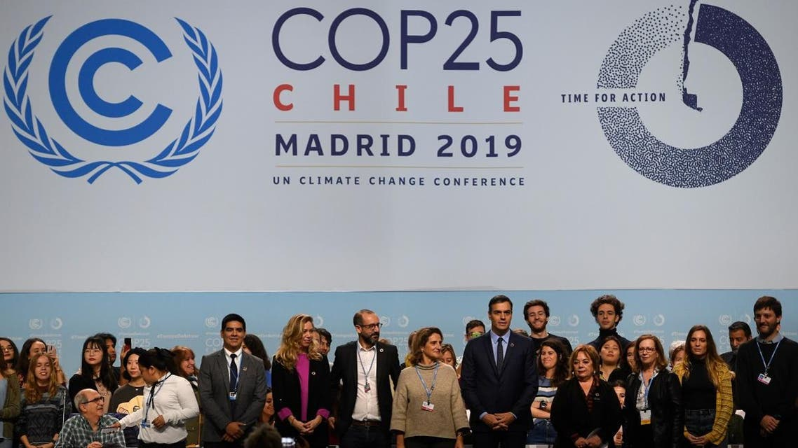Spain's PM Pedro Sanchez (C-R) poses with officials and volunteers in Madrid on November 30, 2019 where the COP25 climate summit will be held. (AFP)