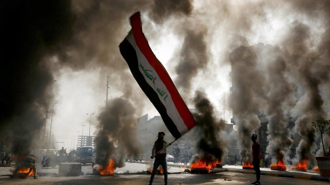 A protester holds an Iraqi flag amid a cloud of smoke from burning tires during ongoing anti-government protests in Najaf, Iraq November 26, 2019. REUTERS