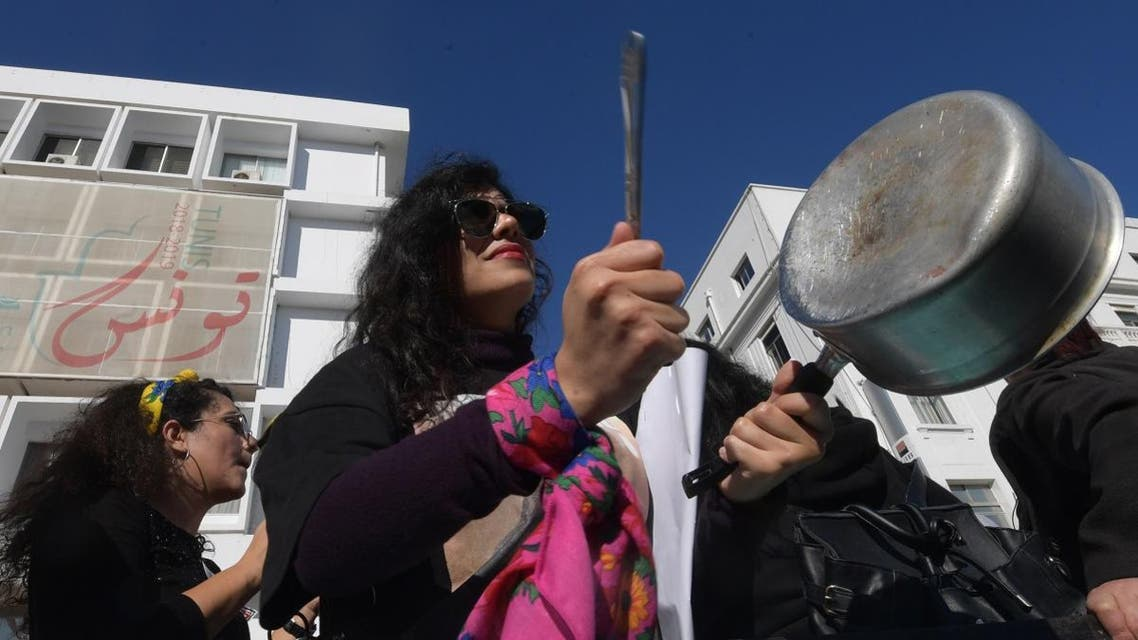"""A Tunisian woman, member of the Tunisian """"EnaZeda"""", (me too in the Tunisian dialect and inspired by the original Metoo movement) bangs a pot as she takes part in a rally against sexual harrasment, in the capital Tunis. (AFP)"""