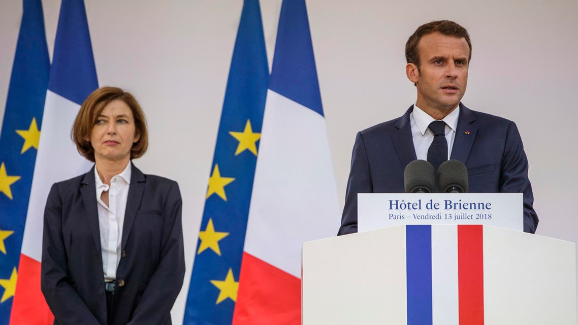 France's President Emmanuel Macron, right, flanked by French Defense Minister Florence Parly, left, delivers a speech after signing the armed forces annual law budget, at the Hotel de Brienne, in Paris, France, Friday, July 13, 2018. (Christophe Petit Tesson/Pool Photo via AP).