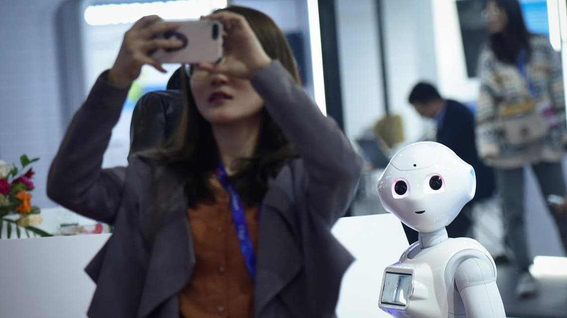 A robot looks at a woman using her mobile phone at China Beijing International High-Tech Expo (CHITEC) in Beijing on October 24, 2019. (AFP)