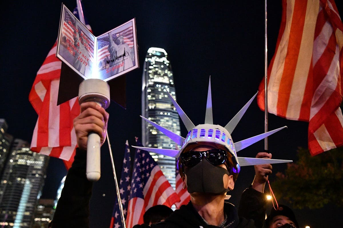 A participant holds a torch and wears headgear modelled after the Statue of Liberty as people assemble for a gathering of thanks at Edinburgh Place in Hong Kong's Central district on November 28, 2019. (AFP)