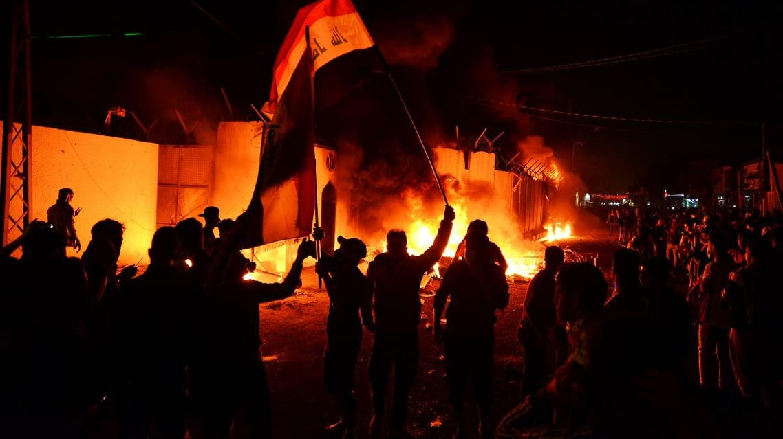Iraqi demonstrators gather as flames start consuming Iran's consulate in the southern Iraqi Shiite holy city of Najaf on November 27, 2019. (AFP)