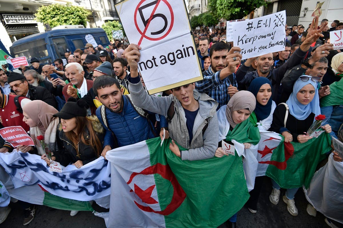 Algerian demonstrators chant slogans against the upcoming presidential election as they carry national flags during an anti-government protest in the center of the capital Algiers on November 26, 2019. (AFP)