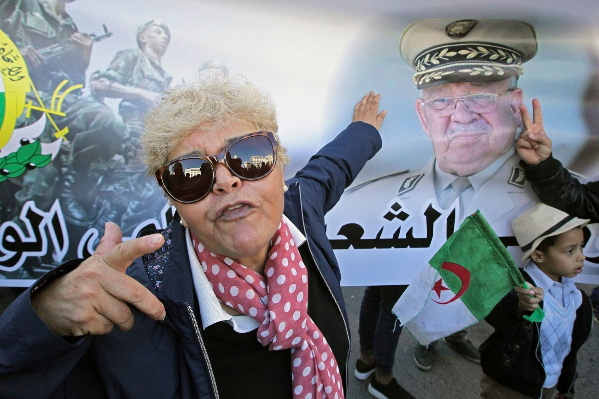 An Algerian woman gestures by a poster showing Algeria's army chief Gen.Ahmed Gaid Salah during a march against EU interference into Algeria's policy. (AP)