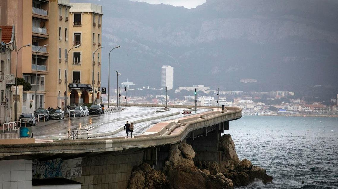 A couple walk along the coast as clouds form over Marseille, France, Sunday, Dec. 1, 2019. The southern France region is under alert for heavy rain and floods. (AP Photo/Daniel Cole)