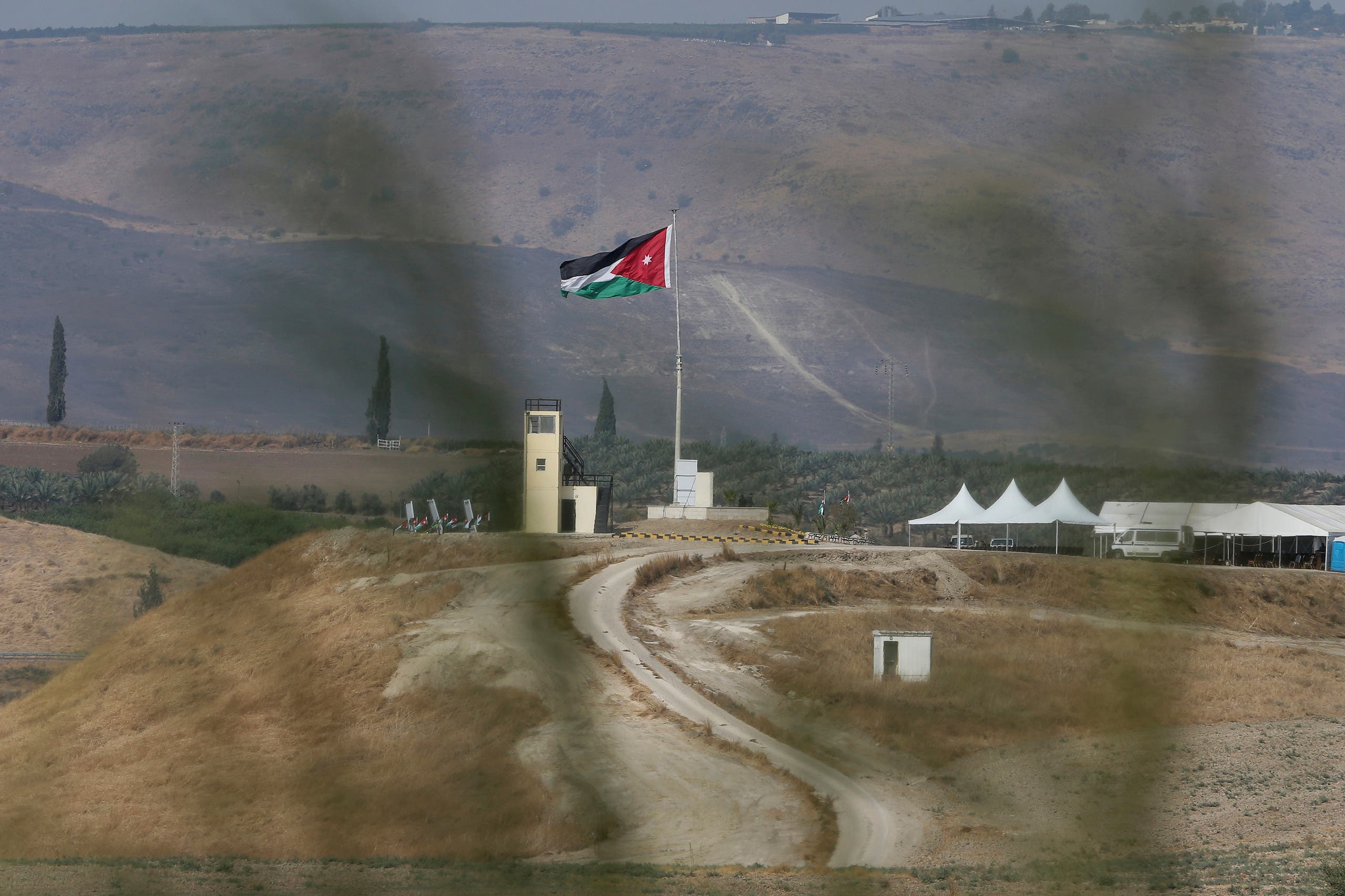 Soldiers stand guard in a watchtower flying Jordanian flags, in the area of ​​Baqoura near the Israeli-Jordanian, border, on Wednesday, Nov. 13, 2019. (AP)