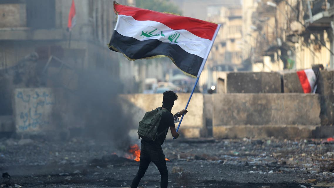 An Iraqi anti-government protester waves a national flag close to a concrete barricade amidst clashes with security forces along the capital Baghdad's Rasheed street near al-Ahrar bridge on November 29, 2019. Iraq's embattled premier announced on November 29 he will resign in keeping with the wishes of the country's top Shiite cleric, after nearly two months of anti-government protests that have cost more than 400 lives.