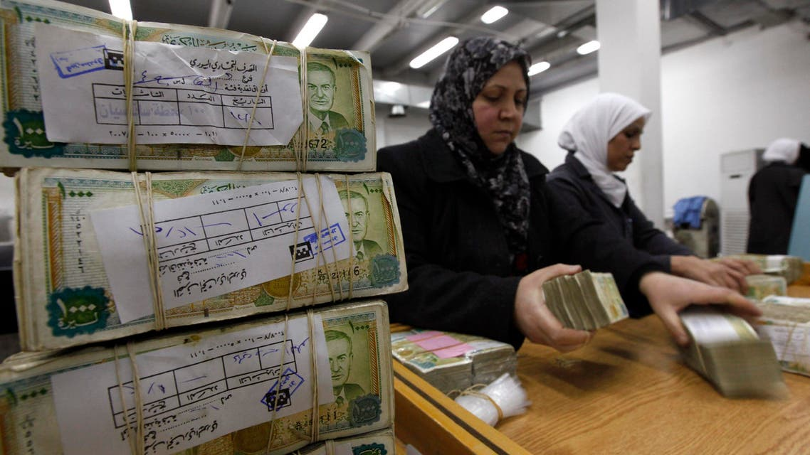 This January 13, 2010 file photo, employees stack Syrian currency in the Central Bank, in Damascus, Syria. (AP)