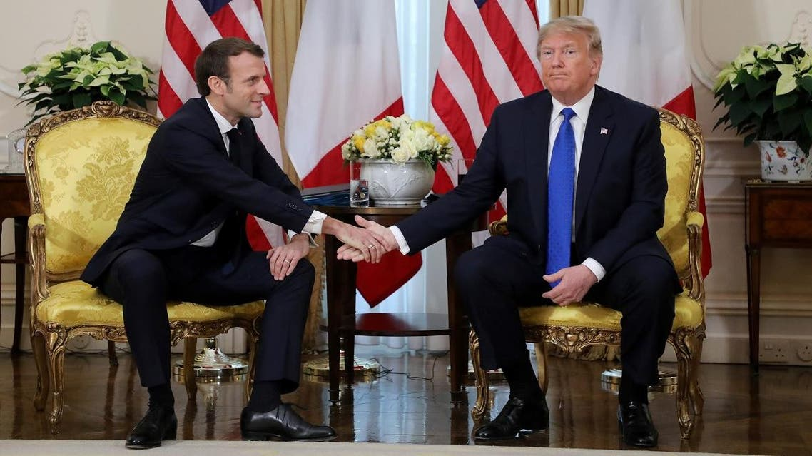 US President Donald Trump and France's President Emmanuel Macron shake hands during their meeting at Winfield House, London on December 3, 2019. (AFP)