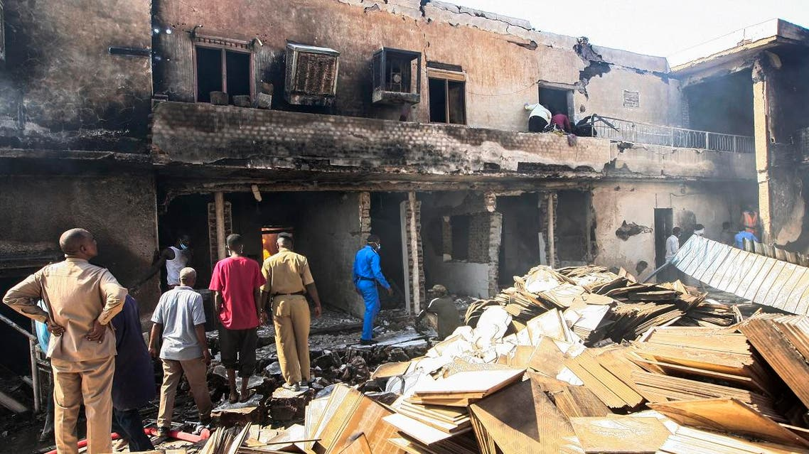 Members of the Sudanese Civil Defence search for victims at the scene of a fire at a tile manufacturing unit in an industrial zone in north Khartoum, on December 3, 2019. (AFP)