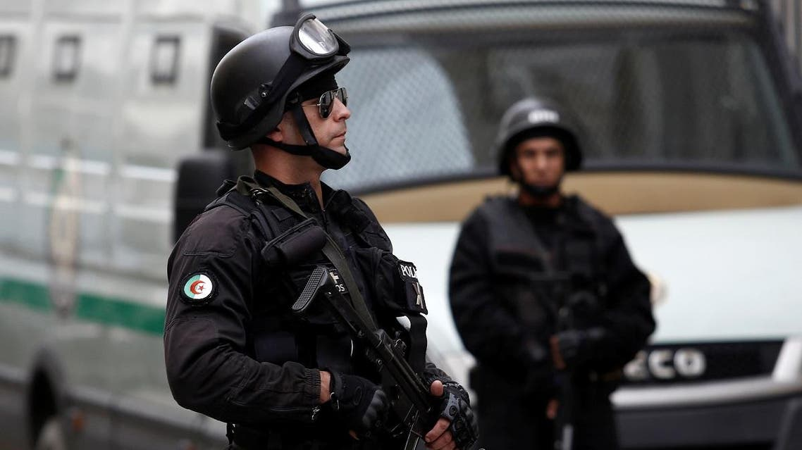Members of the Research and Intervention Brigades stand guard outside a court during the trial of senior officials including two former prime ministers in Algiers. (Reuters)