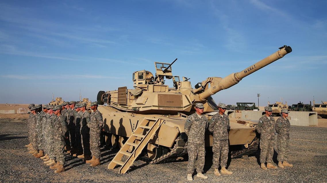 US troops stand at attention next to an Abrams tank at Camp Buehring, Kuwait. (File photo: AFP)